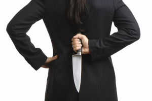 A businesswoman hiding a knife in her back